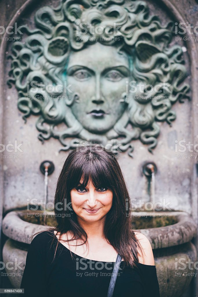 Woman posing in front of medusa fountain stock photo