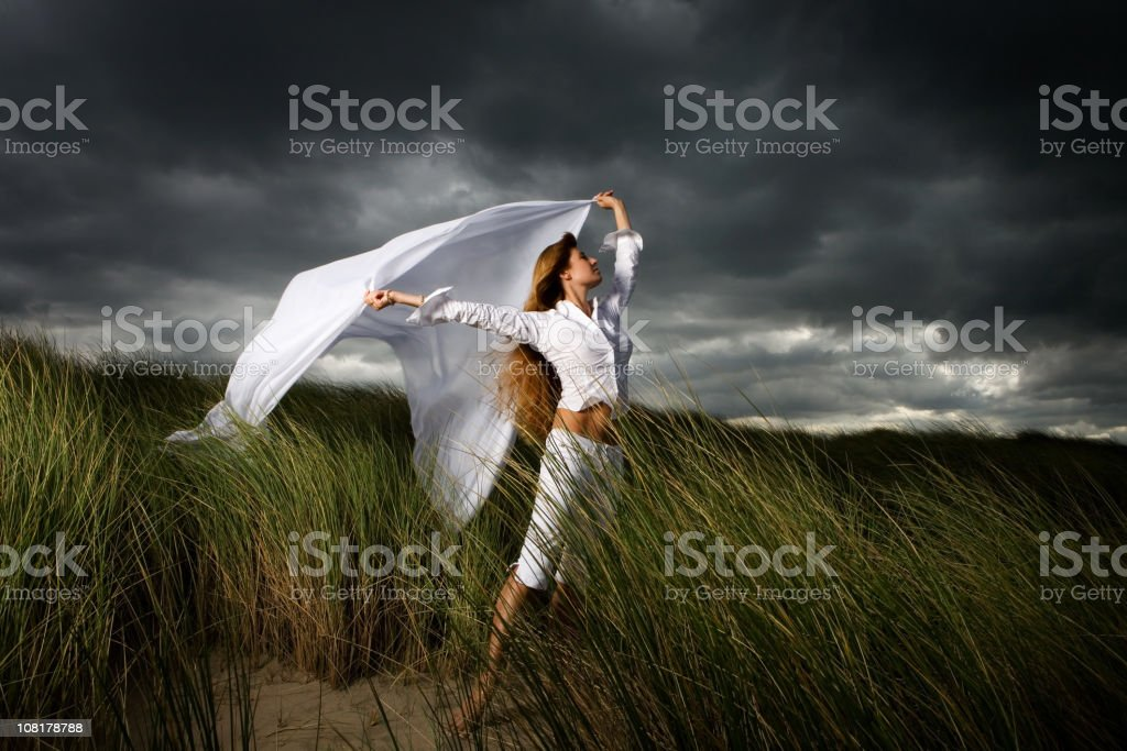 Woman Posing in Sand Dunes and Gray Sky stock photo