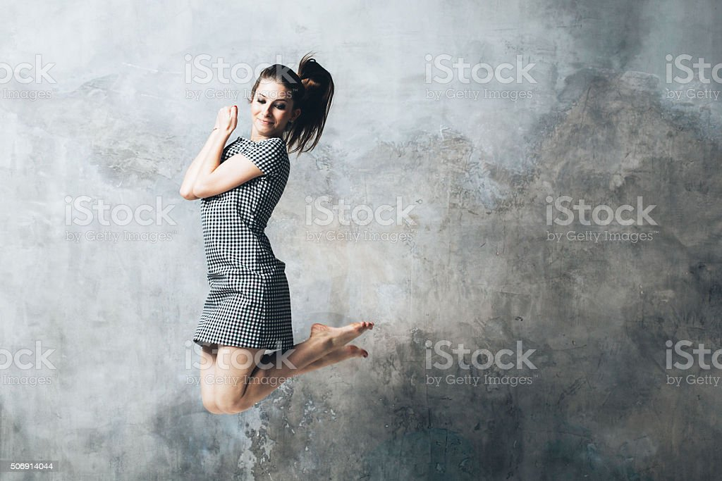 Woman posing near gray background portrait jump stock photo