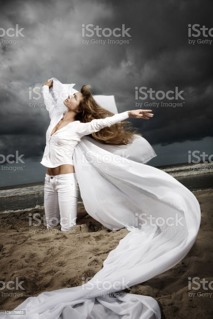 Woman Posing on Beach against moody sky stock photo