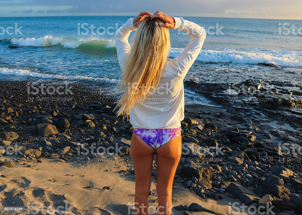 Woman posing on the beach in sunset in bikinis stock photo