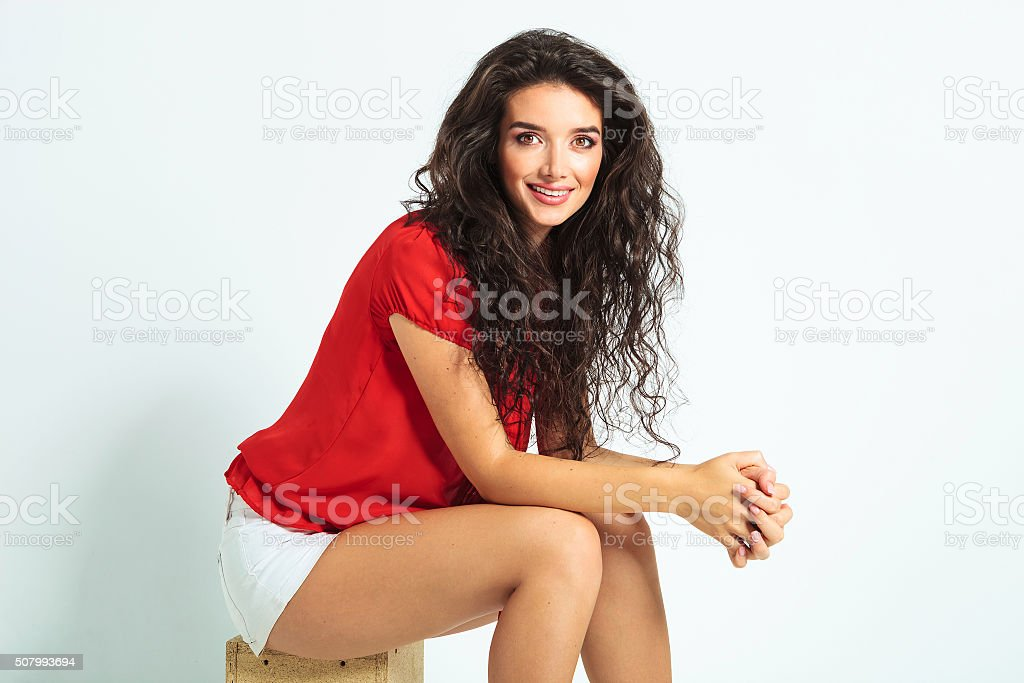 woman posing sitting on a chair stock photo