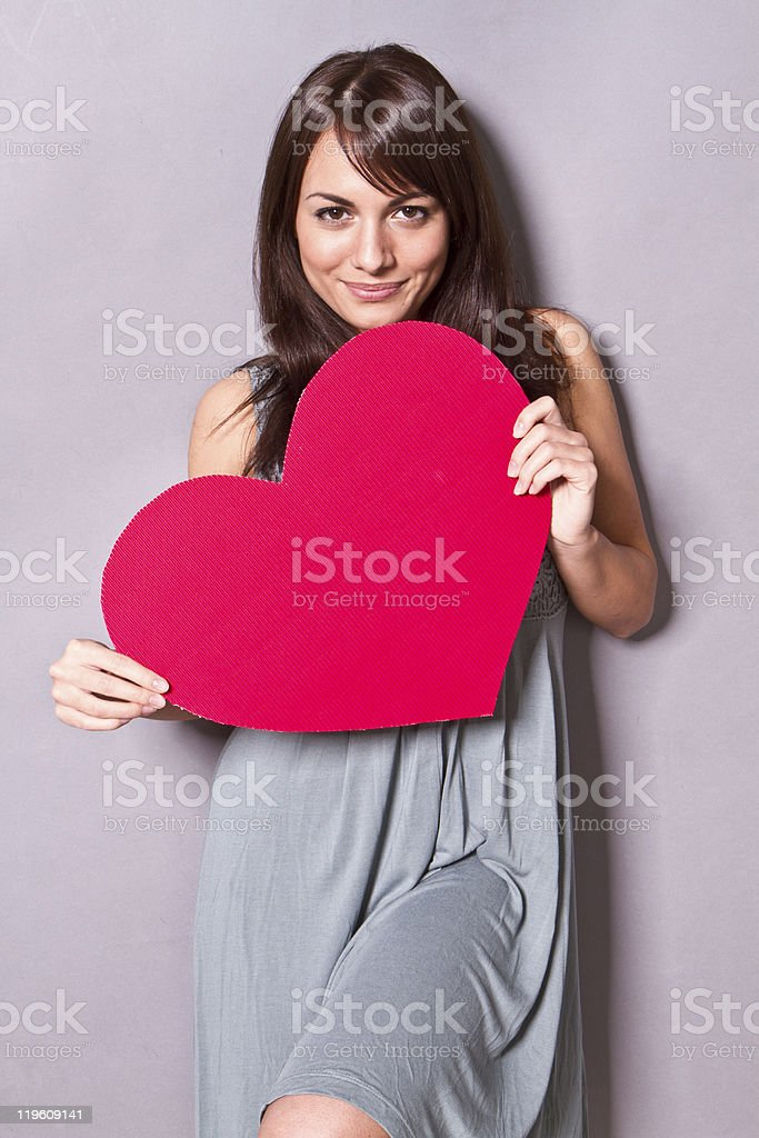 Woman posing with a large red heart shaped poster royalty-free stock photo