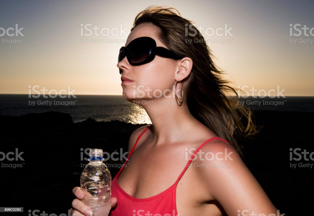Woman posing with sunglasses and water bottle stock photo