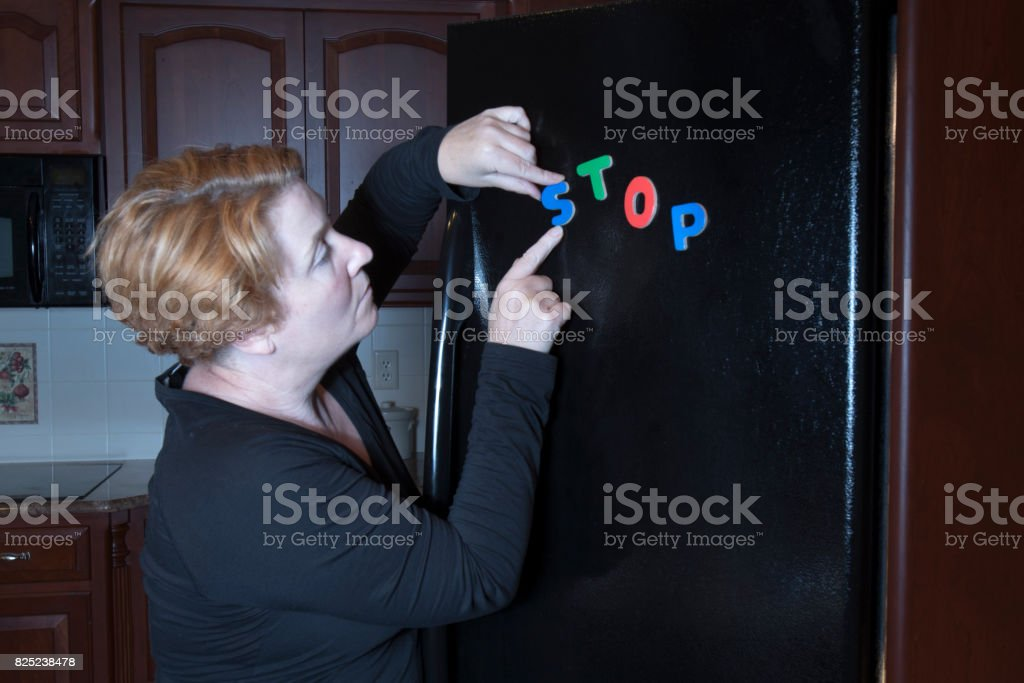 Woman posting dieting motivation message on refrigerator stock photo
