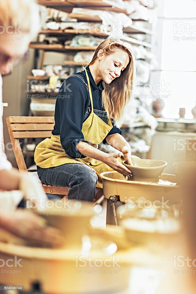 woman potter  in workshop working on pottery wheel stock photo