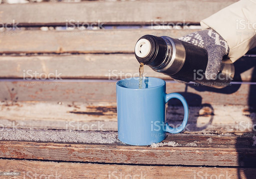 Woman pouring a hot drink in mug from thermos stock photo