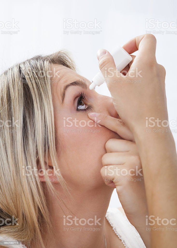 Woman pouring drops in her eyes stock photo