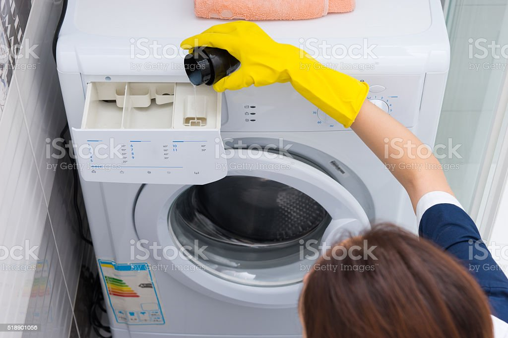 Woman pouring fabric softener into a machine stock photo