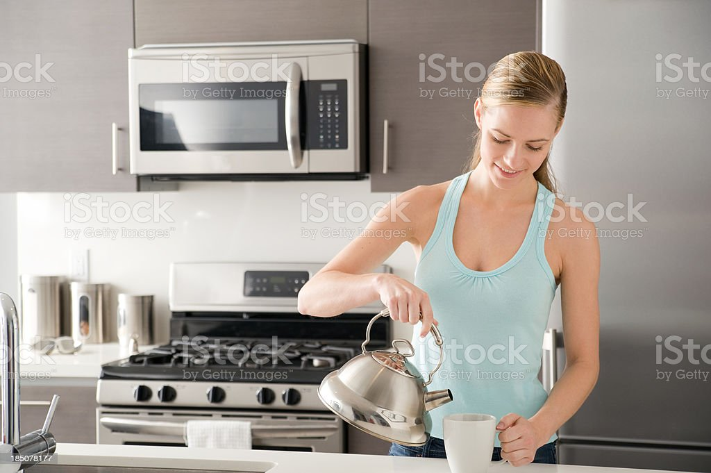 Woman pouring hot water from kettle royalty-free stock photo