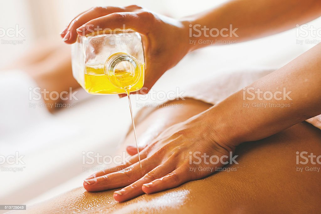 Woman pouring massage oil on spa client stock photo
