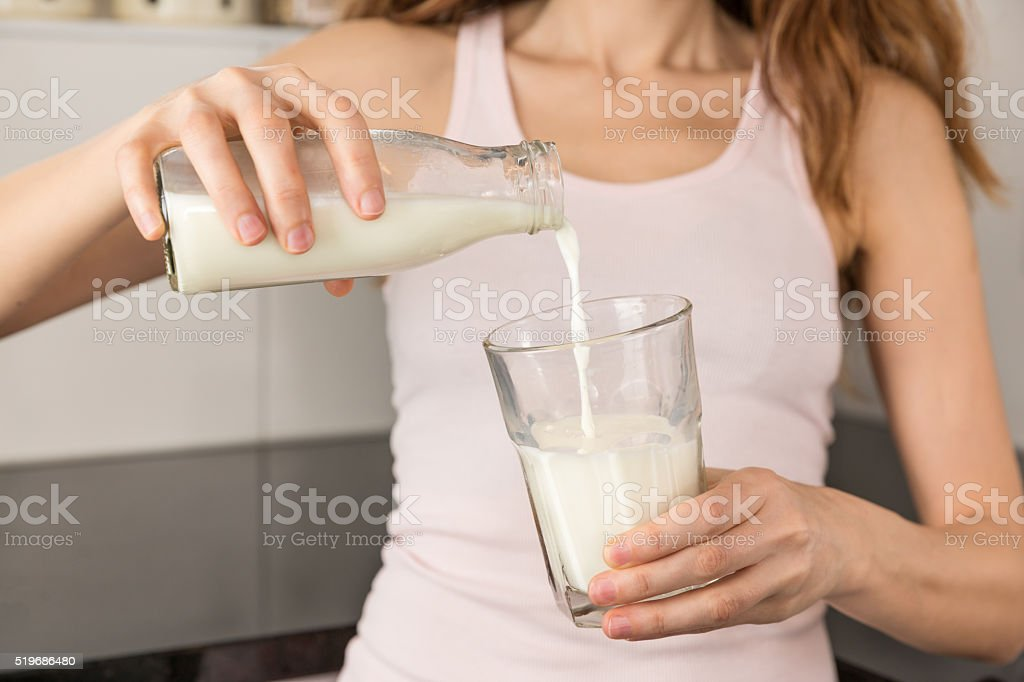 Woman pouring milk from a bottle stock photo