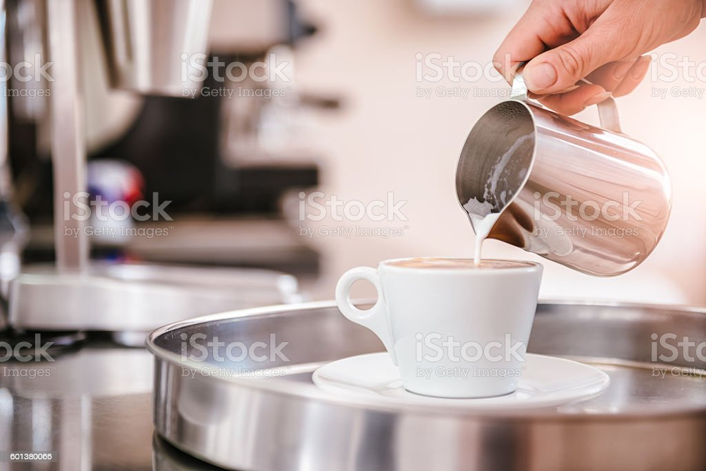 Woman pouring milk in coffee stock photo