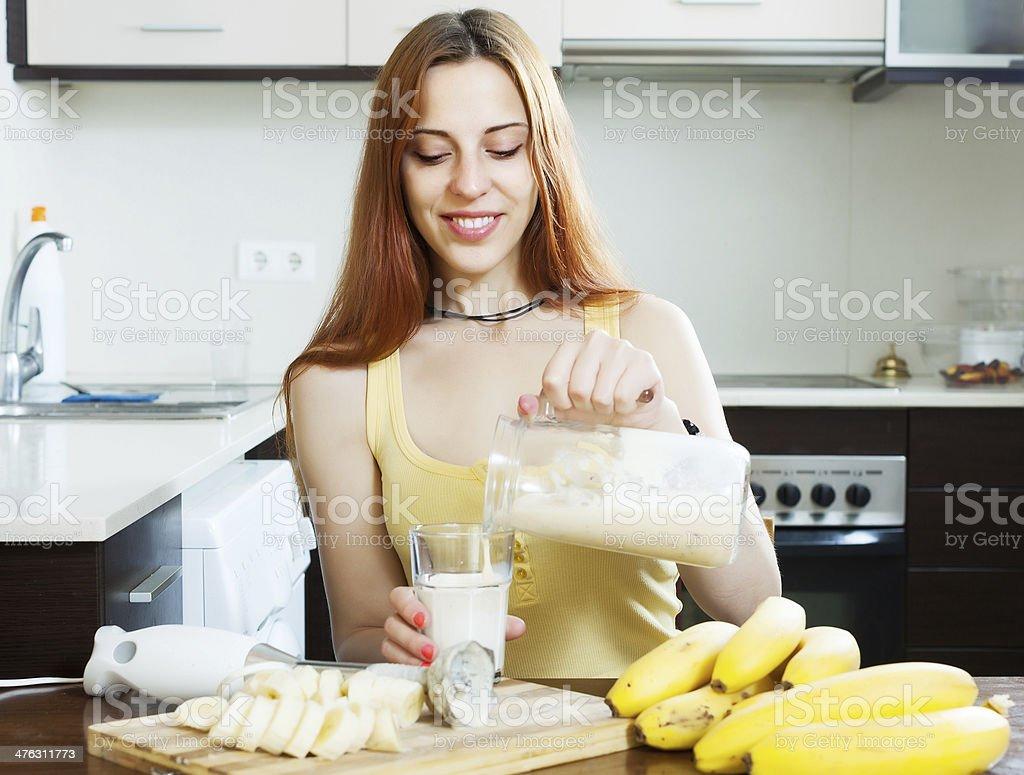 woman  pouring milk shake with bananas royalty-free stock photo