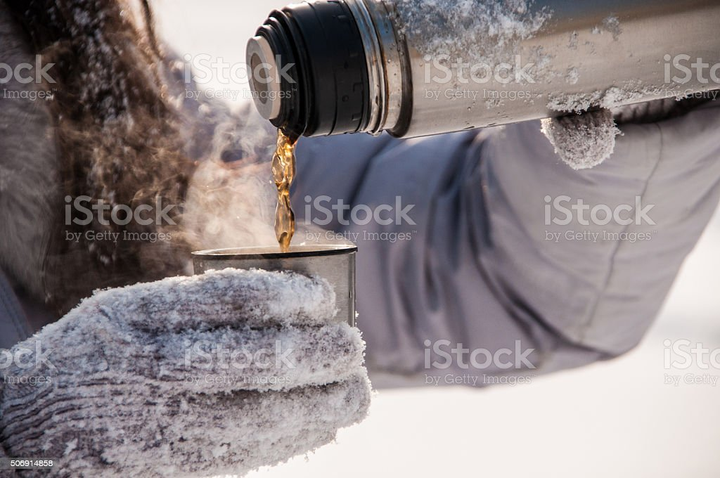 woman pours tea from a thermos winter stock photo