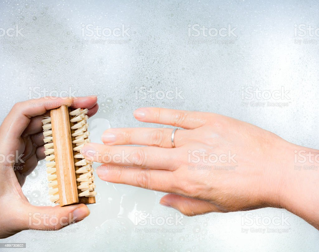 Woman pov cleaning her nails stock photo