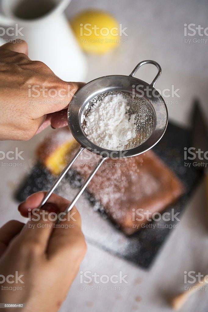 Woman powdering sugar on delicious cake stock photo