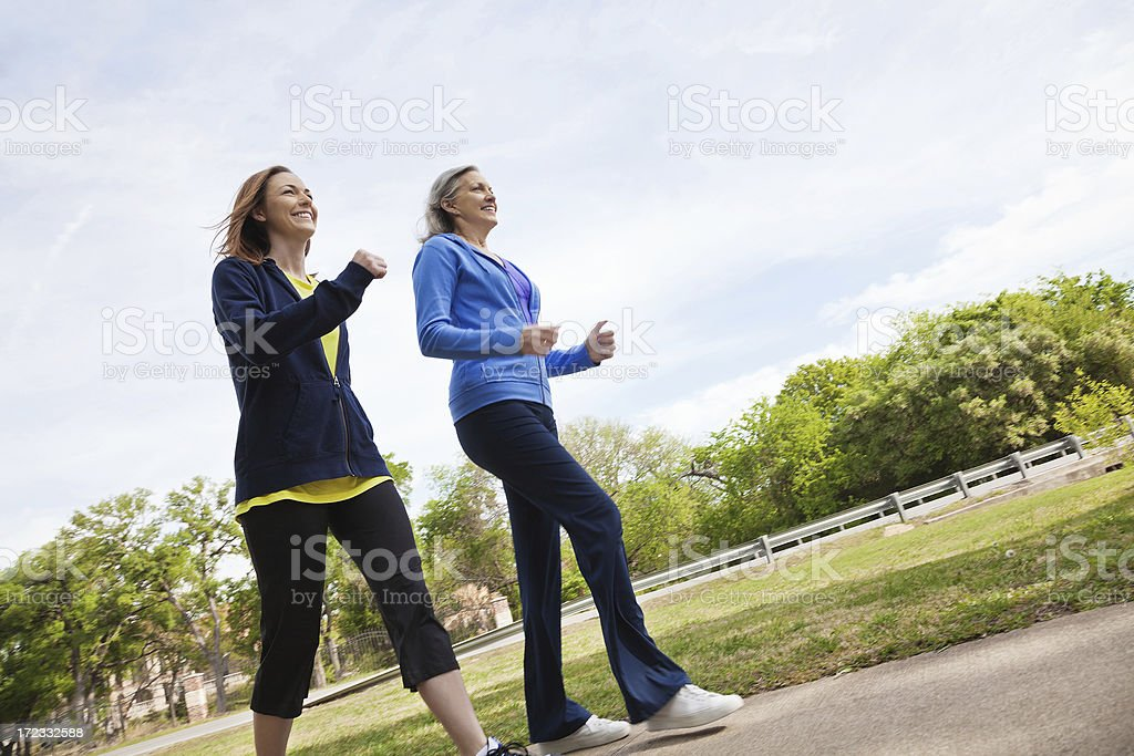 Woman power walking in park with active senior mom stock photo