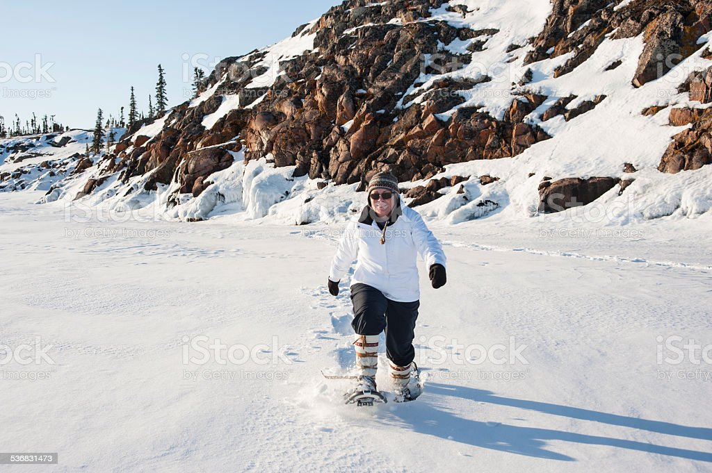 Woman Powers Through Deep Snow on Snowshoes, Great Slave Lake. stock photo