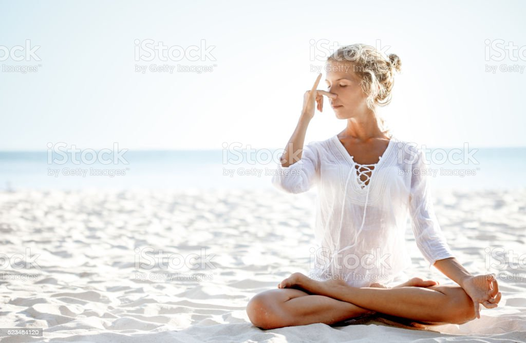 Woman practices pranayama in lotus pose on the beach stock photo