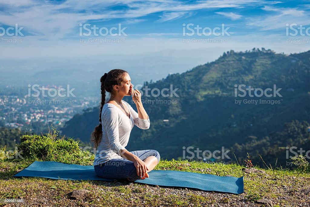 Woman practices pranayama in lotus pose outdoors stock photo