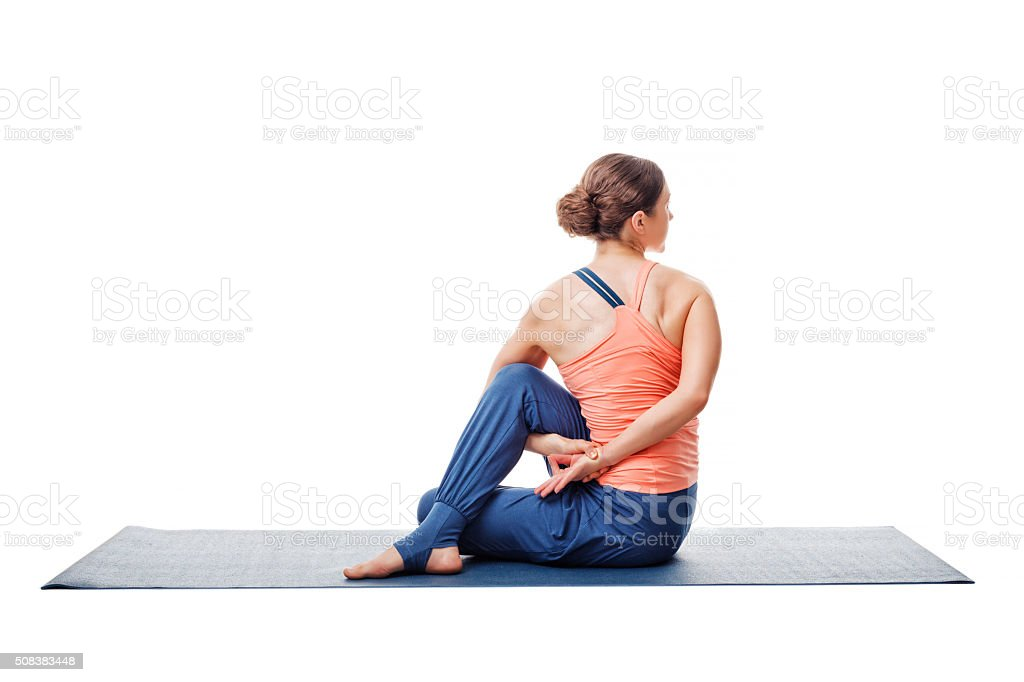 Woman practices yoga asana  Ardha matsyendrasana stock photo