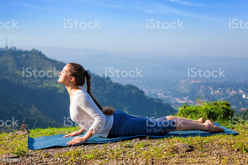 Woman practices yoga asana bhujangasana cobra pose stock photo