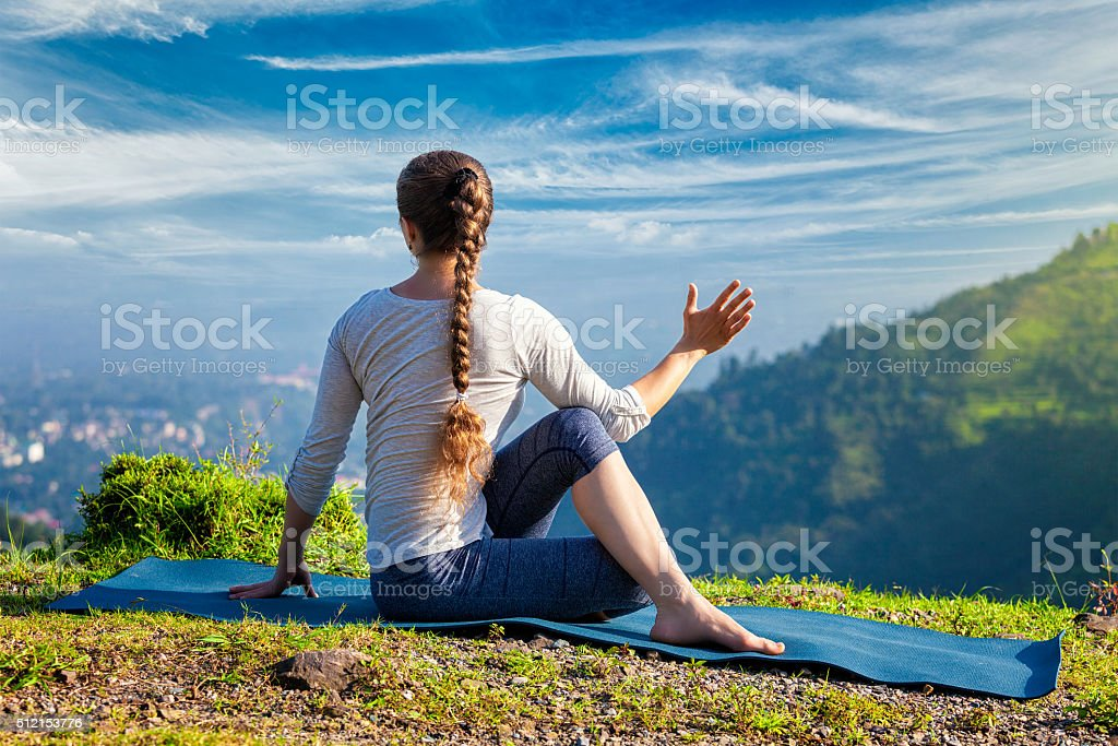 Woman practices yoga asana Marichyasana stock photo