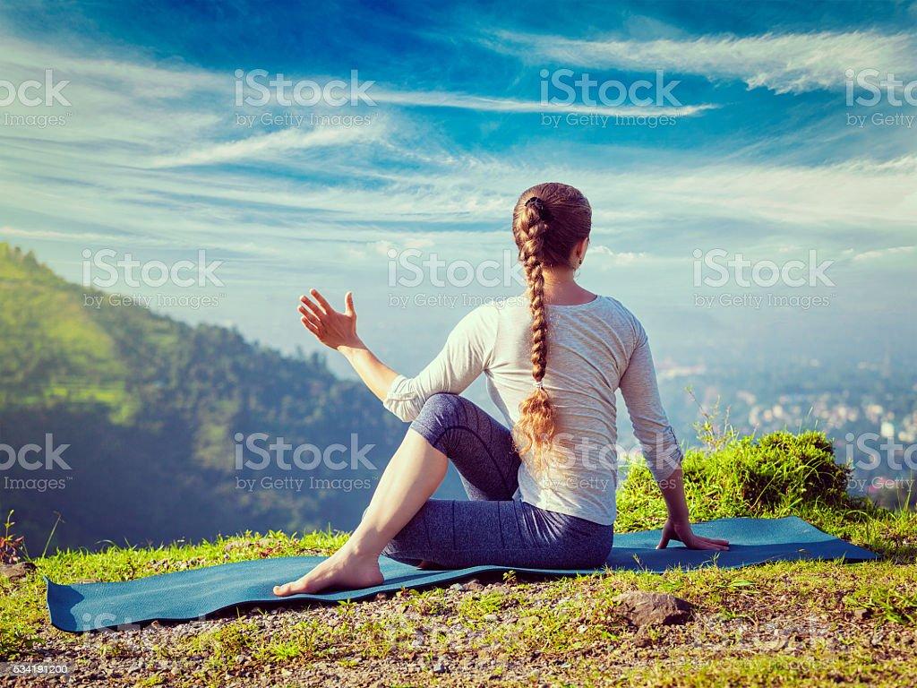 Woman practices yoga asana Marichyasana stock photo