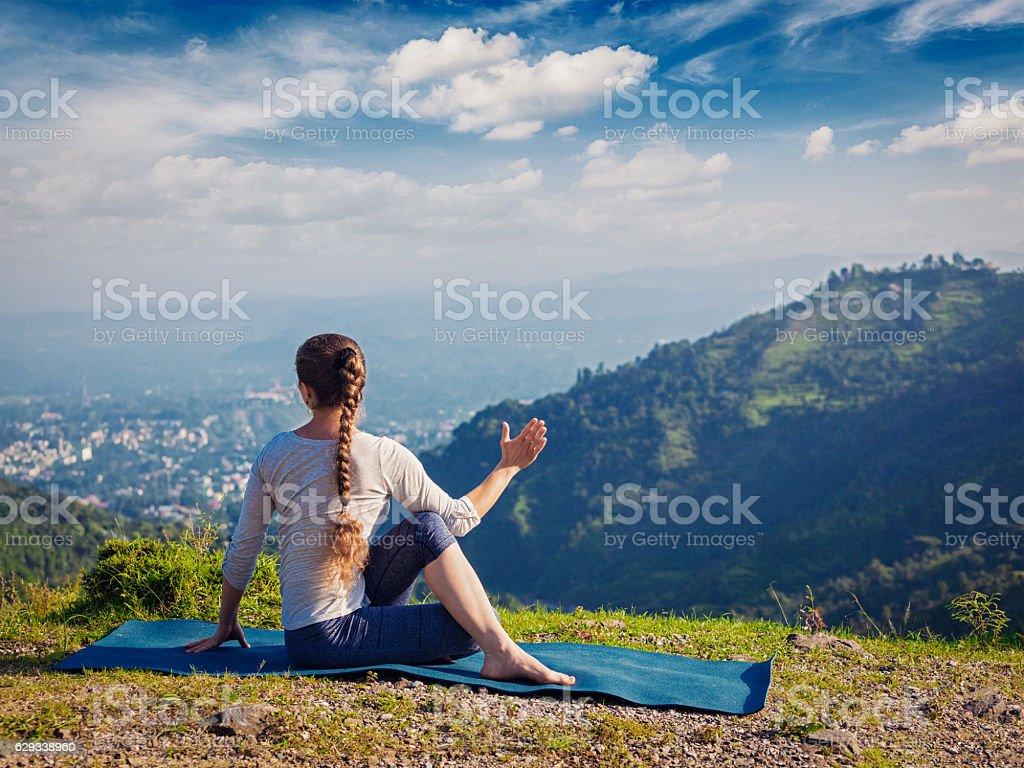 Woman practices yoga asana outdoors stock photo