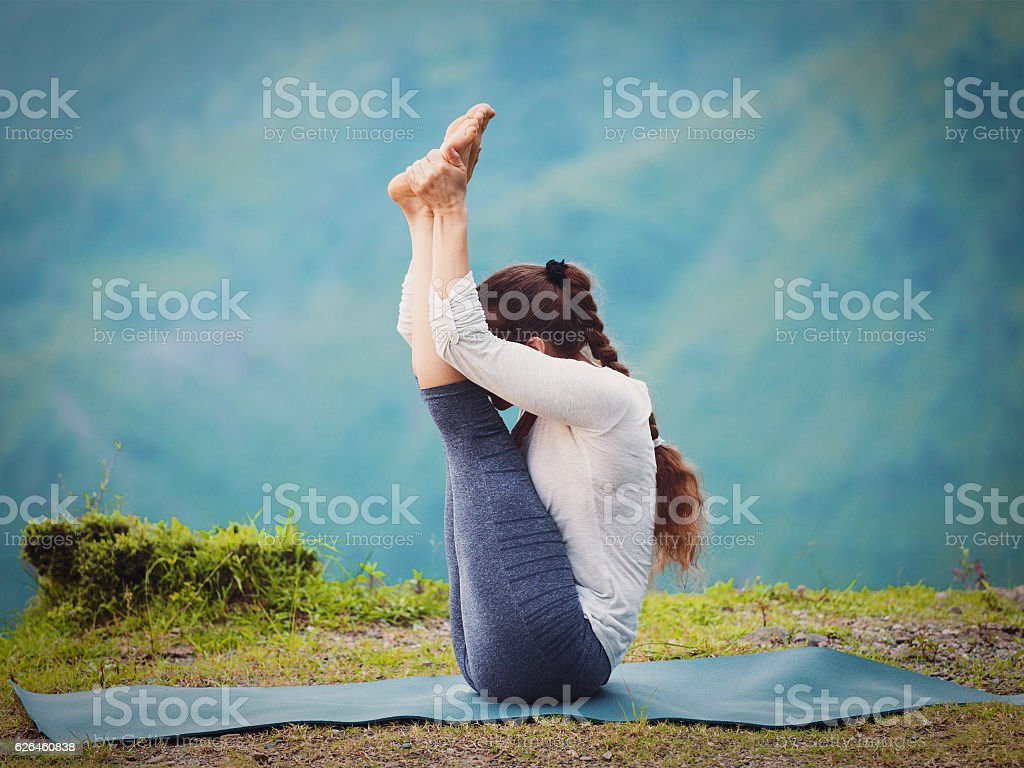 Woman practices yoga asana Urdhva mukha paschimottanasana stock photo
