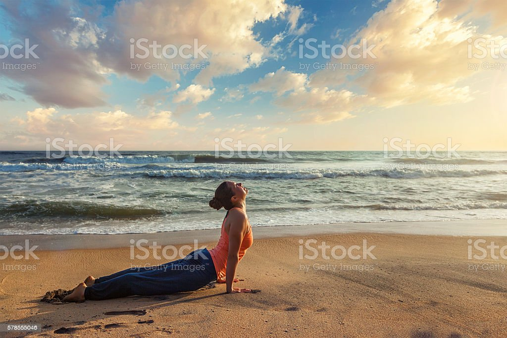 Woman practices yoga asana Urdhva Mukha Svanasana at the beach stock photo