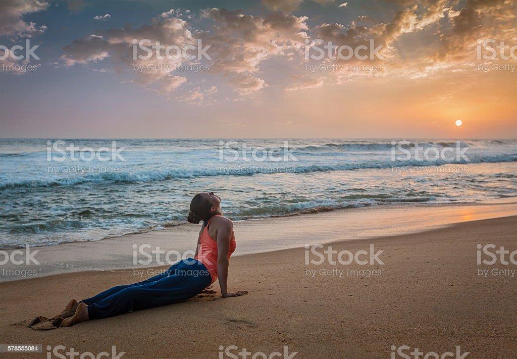 Woman practices yoga asana Urdhva Mukha Svanasana at the beach stock photo