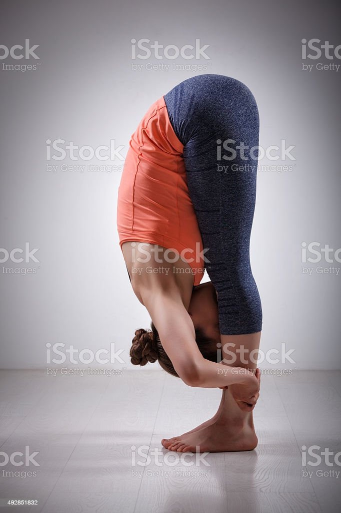 Woman practices yoga asana Uttanasana stock photo