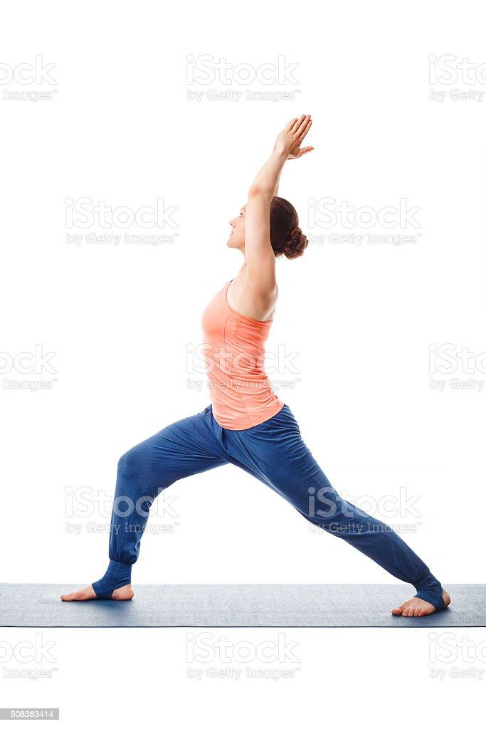 Woman practices yoga asana utthita Virabhadras stock photo
