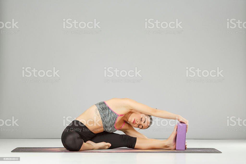 Woman practicing advanced yoga  Pilates stretching training  Yoga block poses stock photo