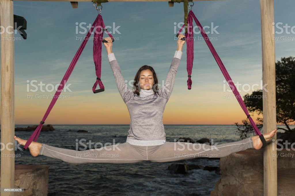 Woman practicing aerial yoga outdoors at sunset stock photo