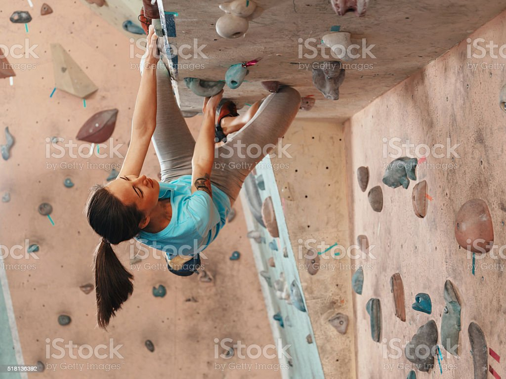 Woman practicing in climbing gym stock photo