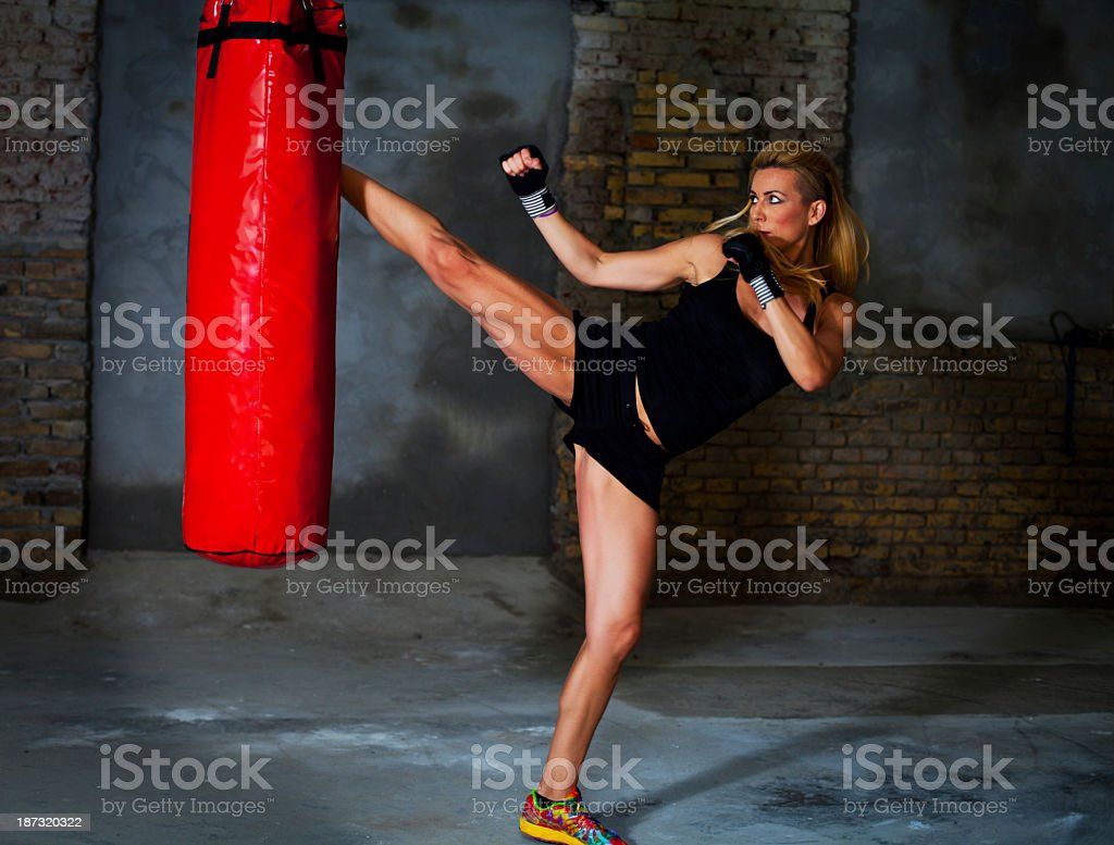 Woman practicing kickboxing using a red punching bag stock photo