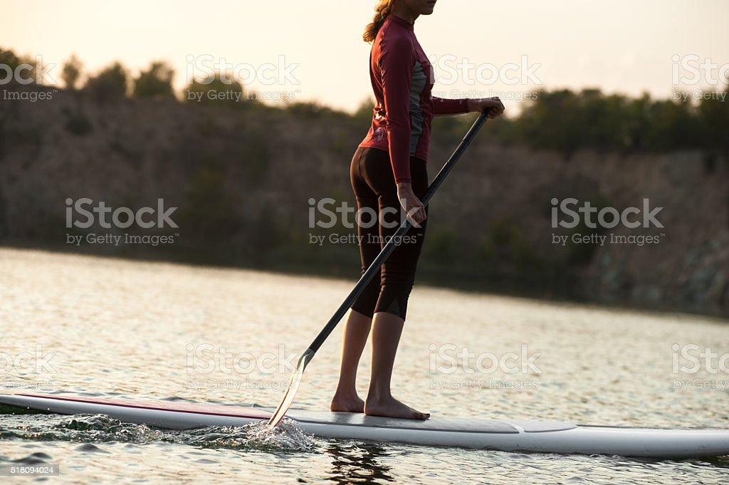 woman practicing paddle sunset stock photo
