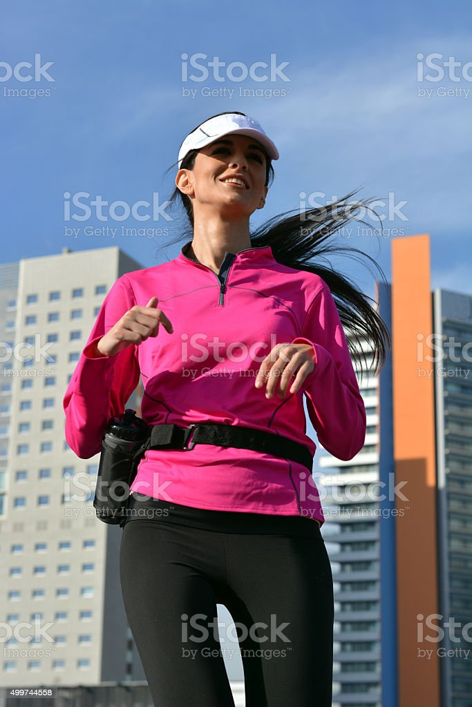 woman practicing running in the city stock photo