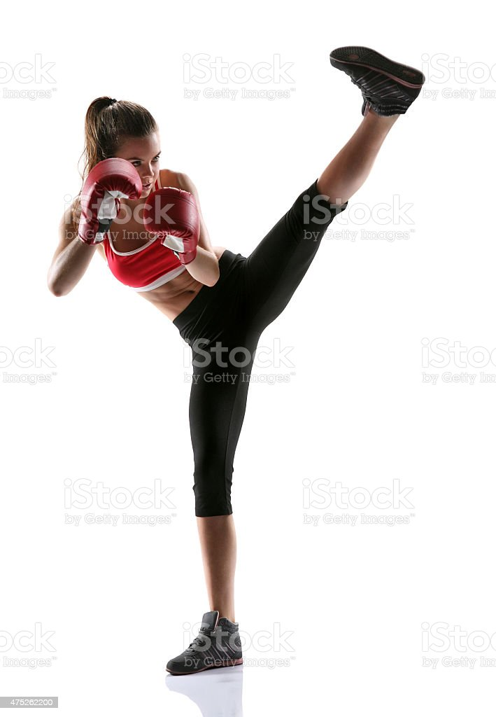 Woman practicing tae-bo exercises, kicking forward with legs stock photo