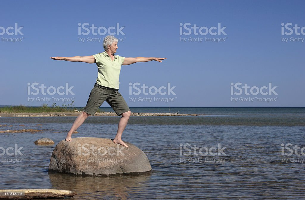 Woman Practicing  Tai Chi on Rock in Water royalty-free stock photo