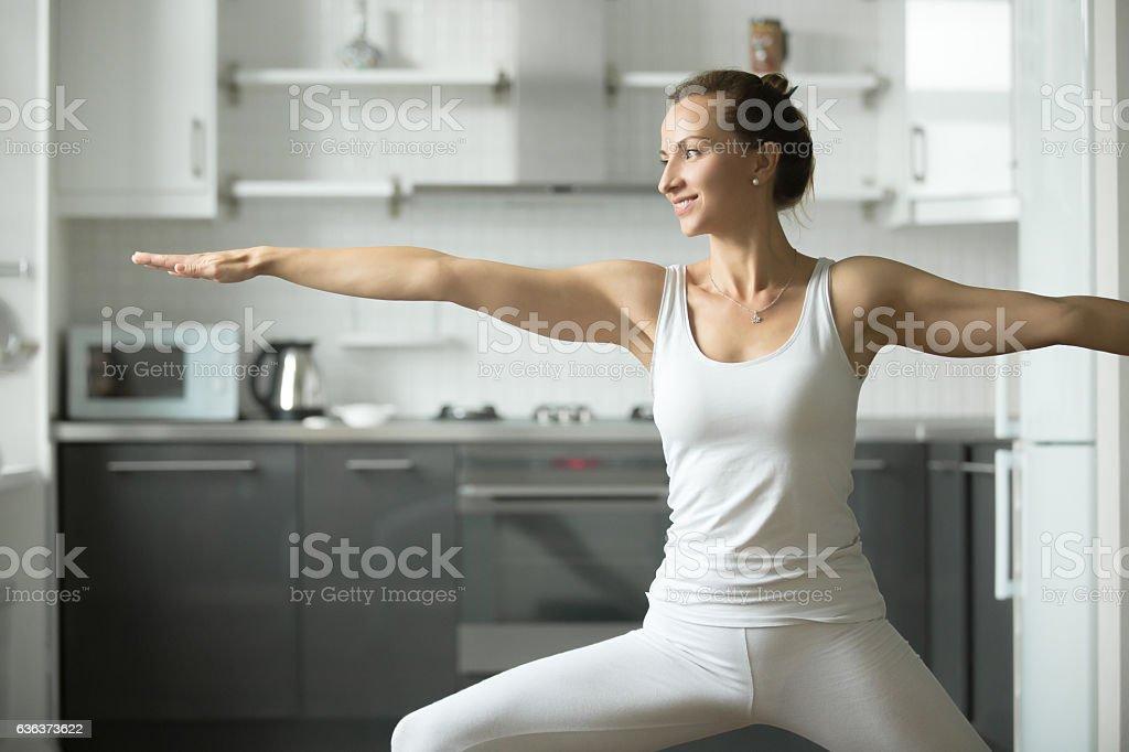 Woman practicing Warrior 2 stock photo