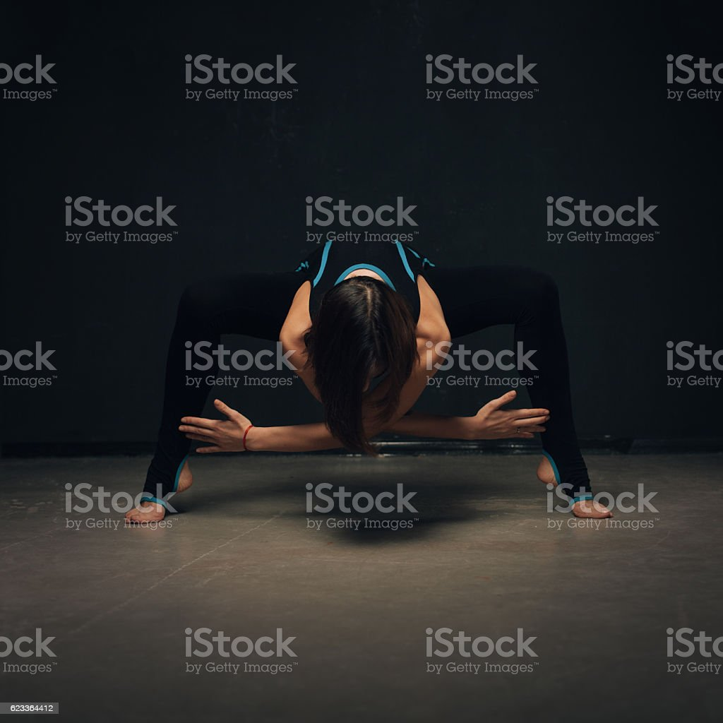 Woman practicing yoga against a dark texturized wall stock photo