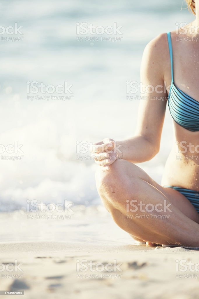 Woman practicing yoga at beach royalty-free stock photo
