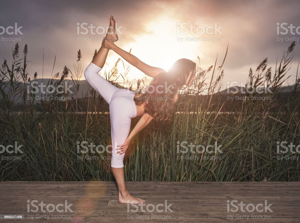 Woman practicing yoga at sunset stock photo