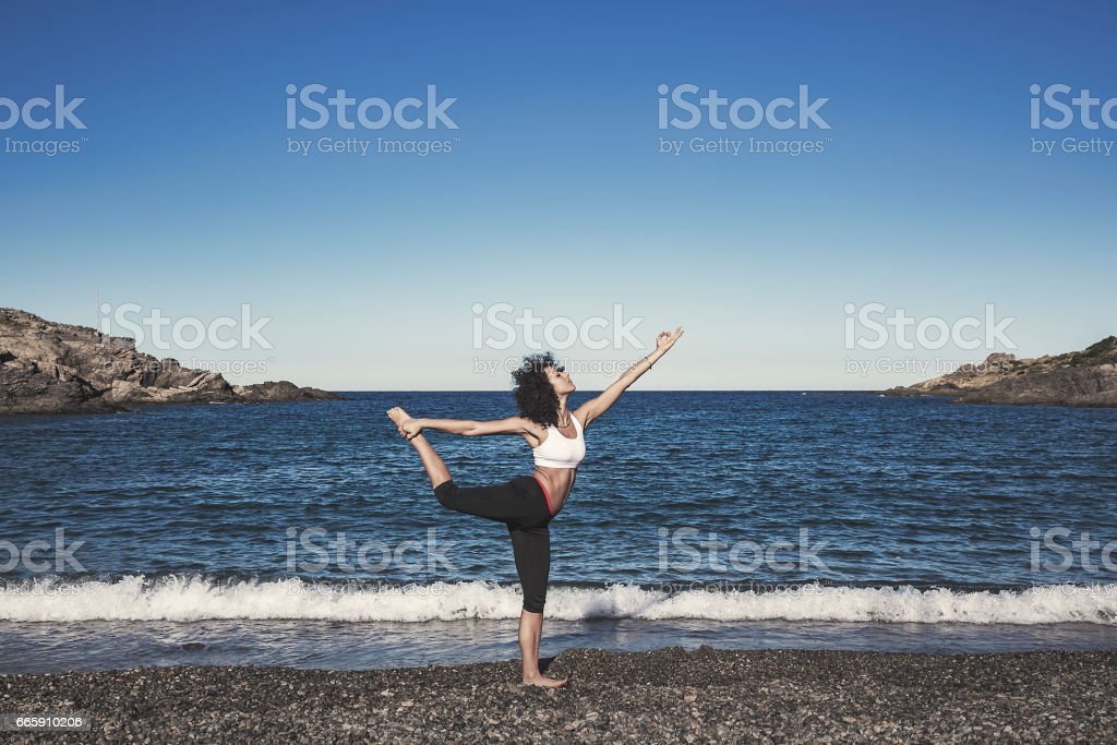 Woman practicing yoga at the beach stock photo