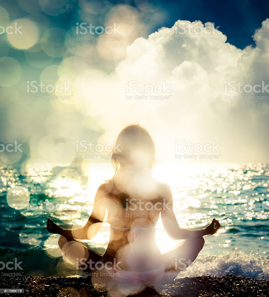 Woman Practicing Yoga by the Sea. Bokeh Background stock photo