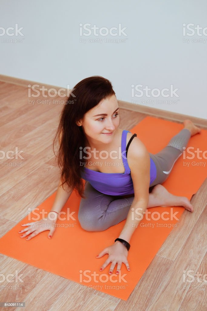 Woman practicing yoga in a studio. Young slim sporty girl practicing...
